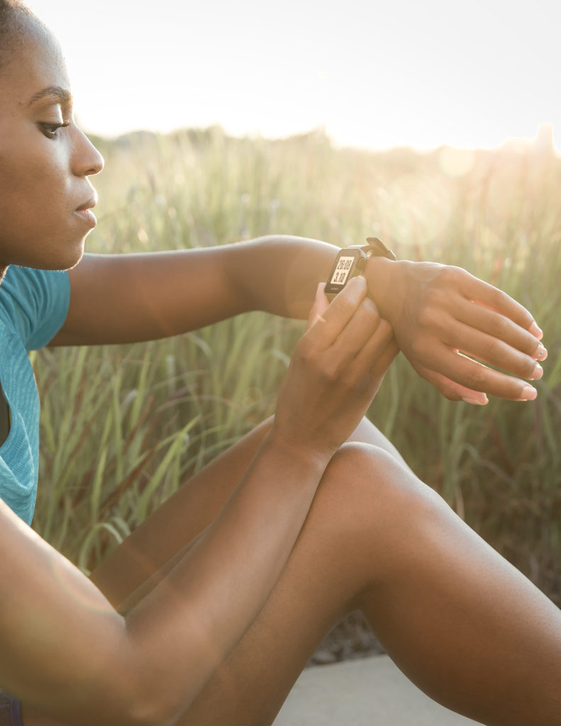 Une femme regarde sa montre après sa course à pied
